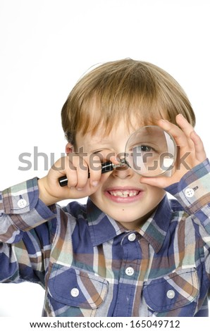 funny boy looking through magnifying glass with surprise  - stock photo