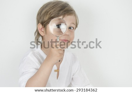 funny boy looking through magnifying glass with surprise