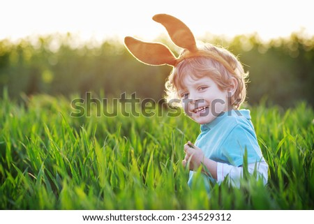 Funny boy of 3 years with Easter bunny ears playing in green grass on sunny spring day, celebrating Easter holiday - stock photo