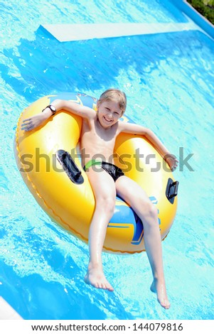 funny boy  on ring in the pool - stock photo
