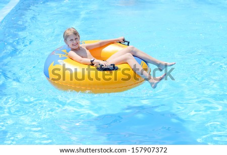 funny boy on ring in the pool