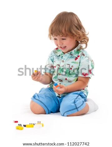 funny boy playing with construction set over white background - stock photo