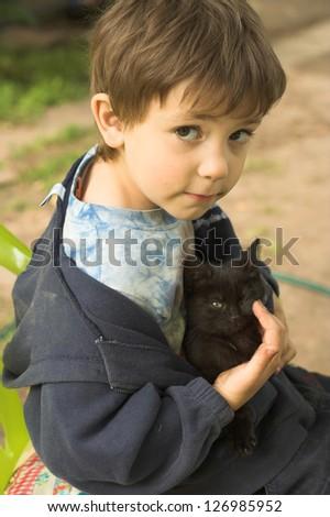 funny boy with black kitten - stock photo