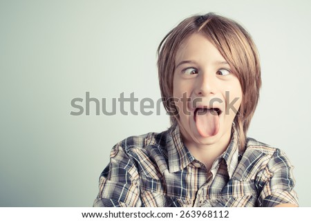 funny boy with cross-eyed and tongue out - vintage style photo - stock photo