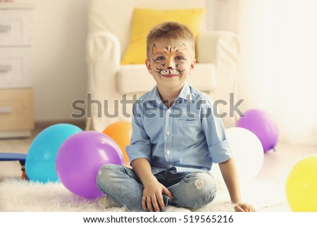Funny boy with face painting in his room