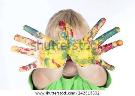 funny boy with hands painted in colorful paint - stock photo