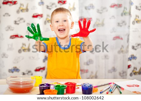 funny boy with painted fingers, painting at home - stock photo