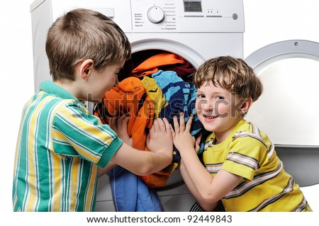 Funny boys loading clothes to washing machine. - stock photo