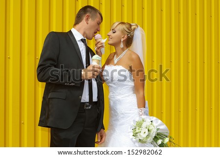 funny bride and groom eat ice cream yellow background - stock photo
