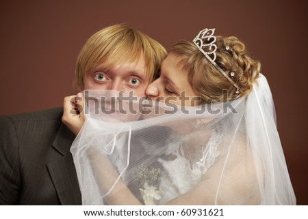 Funny bride and groom were closed veil - stock photo