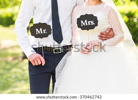 Funny bride and groom with Mr and Mrs signs. Happy wedding day - stock photo