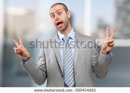 Funny businessman doing victory sign with both hands - stock photo
