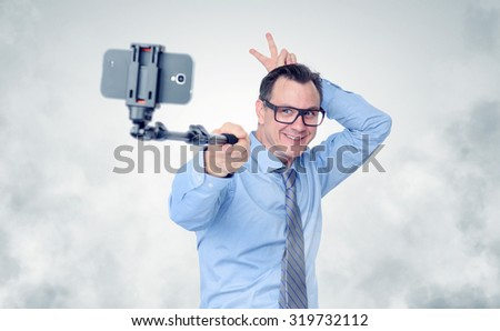 Funny businessman in glasses making selfie with a stick - stock photo