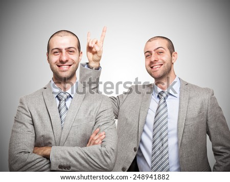 Funny businessman making the horns sign to himself - stock photo