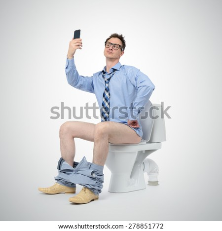 Funny businessman photographing himself in the toilet. Selfie everywhere concept - stock photo
