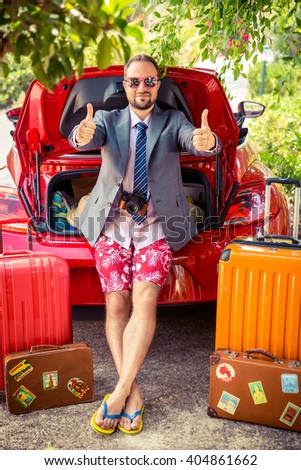 Funny businessman ready to trip. Man standing near red car. Summer vacations and travel concept