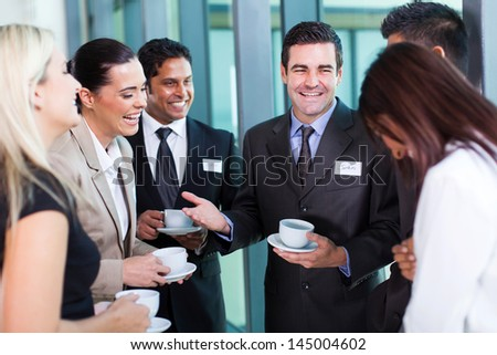 funny businessman telling a joke during conference coffee break - stock photo