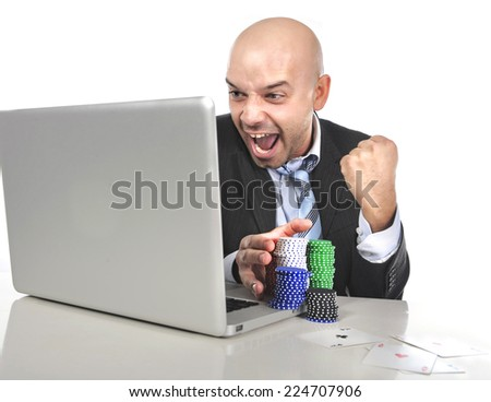funny businessman with stacks of poker chips and playing cards gambling on laptop computer excited winning money in internet gambling addiction and online bets - stock photo