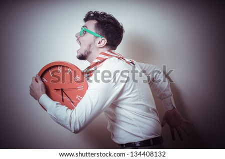 funny businessman with wall clock on gray background - stock photo