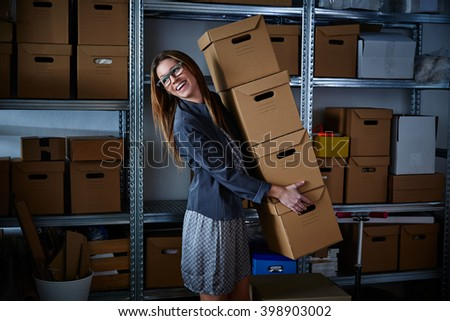 funny businesswoman holding many storage boxes in office warehouse rack - stock photo