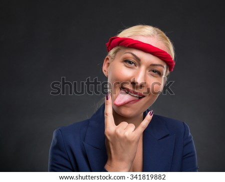 Funny businesswoman showing heavy metal hand gesture over gray background - stock photo