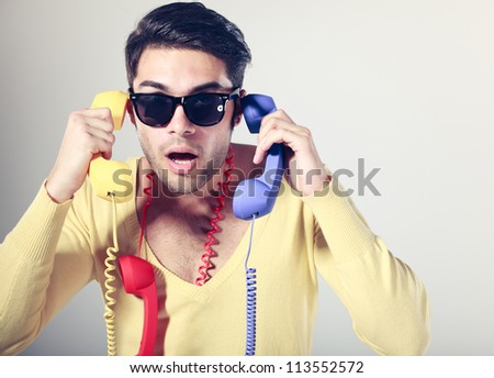 funny call center guy with hipster glasses and colouful phones - stock photo
