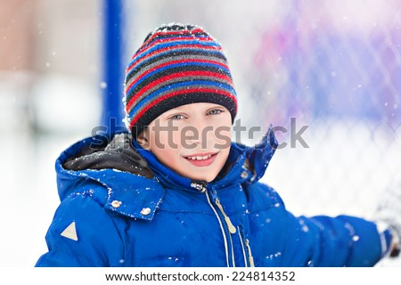 Funny cheerful boy in jacket and hat playing outdoors in winter smiling - stock photo