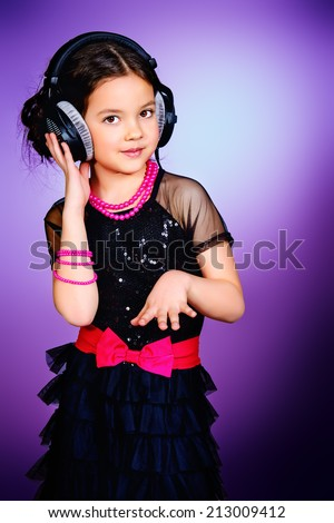 Funny cheerful girl listens to music on headphones. Childhood. - stock photo