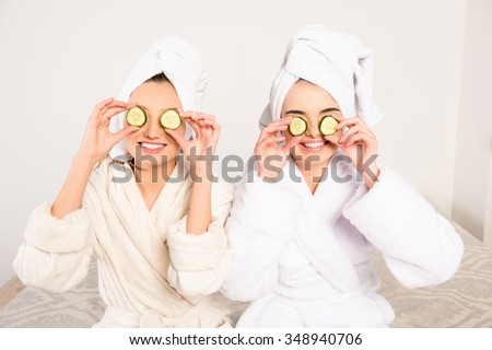 Funny cheerful young women with cucumbers on eyes and towel on their heads - stock photo