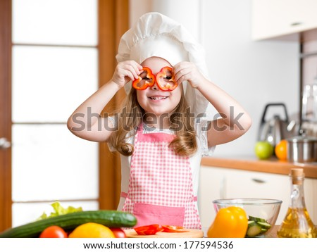 Funny chef girl cooking at kitchen - stock photo