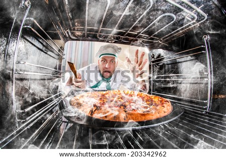 Funny chef overlooked pizza in the oven, so she had scorched, view from the inside of the oven. Cook perplexed and angry. Loser is destiny! - stock photo