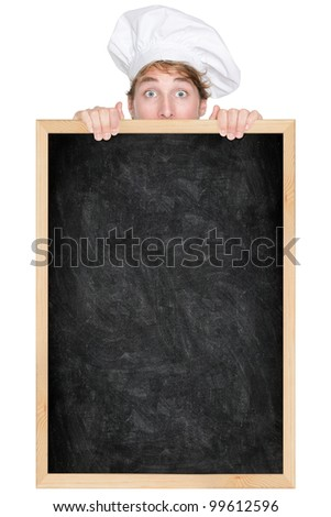 Funny chef showing blank empty blackboard menu sign for restaurant menu or recipe. Man chef cook or baker hiding behind chalkboard peeking over funny. Isolated on white background. - stock photo