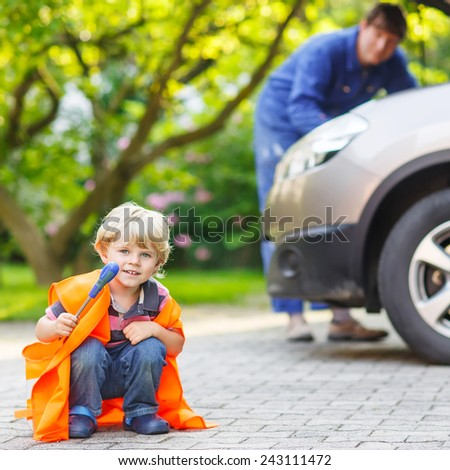 Funny child in orange safety vest during his father repairing family car on background. Vehicle breakdown on travel trip. Safety on roads concept - stock photo