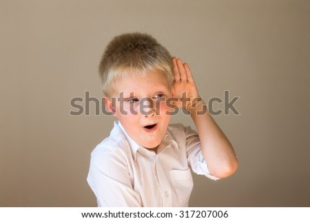 Funny child listening overhearing something with hand to ear concept - stock photo