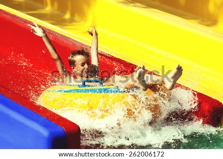Funny child playing in water park splashing water. Summer holidays concept. - stock photo
