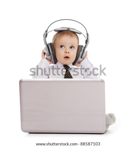 Funny child playing with laptop and listening to music in headphones - stock photo