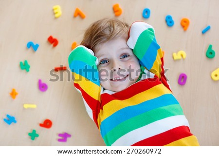 Funny child playing with lots of colorful plastic digits or numbers, indoor. Kid boy wearing colorful shirt and having fun with learning math - stock photo