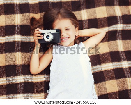 Funny child shooting vintage old retro camera and having fun on the plaid, top view - stock photo