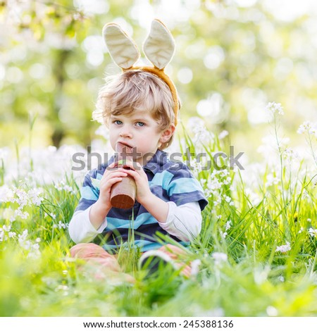 Funny child wearing Easter bunny ears at spring green grass and blooming apple garden, eating chocolate bunny and having fun outdoors. After traditional egg hunt. - stock photo