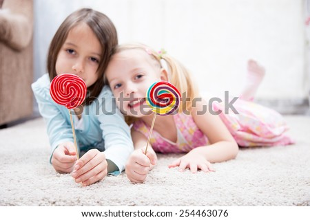 Funny child with candy lollipop, happy little girl eating big sugar lollipop - stock photo