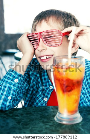 Funny child with party sunglasses drinking a fruit cocktail from a big glass sitting at a table in a restaurant smiling - stock photo