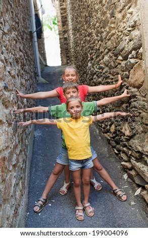 Funny children on narrow street of Canillo, Andorra - stock photo