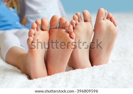 Funny children's foots is barefoot, closeup. This is the concept of friendship, trust and serenity.