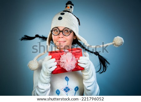 Funny christmas girl with a gift in their hands - stock photo