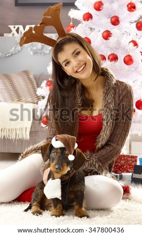 Funny christmas photo with happy woman in reindeer antler and dog in hat. - stock photo