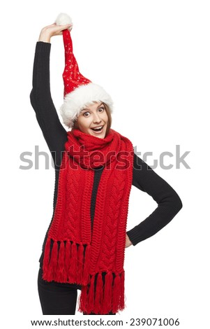 Funny Christmas woman surprised wearing Santa hat pulling her Santa hat pompon, looking away at blank copy space with mouth open in amazement - stock photo