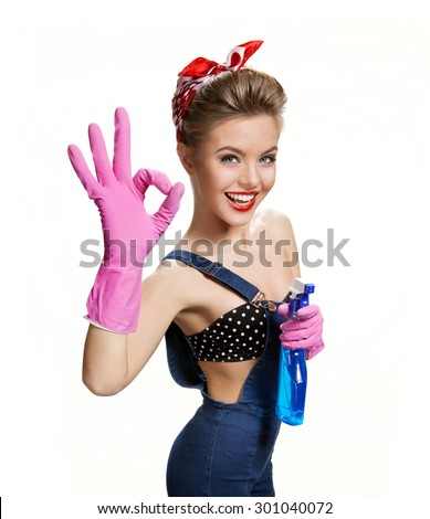 Funny cleaning lady holding spray bottle and showing okay gesture / young beautiful woman wearing pink rubber protective gloves over white background. Cleaning service concept - stock photo