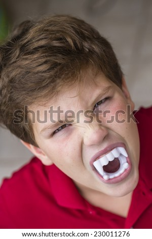 Funny color photo with the expression of a nine year old, white, with vampire teeth, scaring, celebrating halloween - stock photo