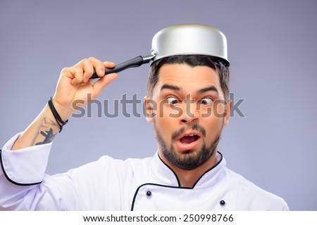 Funny cook. Closeup portrait of handsome cook making faces with a small pan on his head while standing over grey background with copy space - stock photo