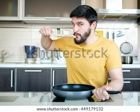 Funny cooking. Attractive caucasian man in the kitchen - stock photo